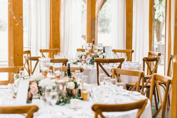 Wedding table styling for rustic reception with wooden detailing and gypsophila bouquets