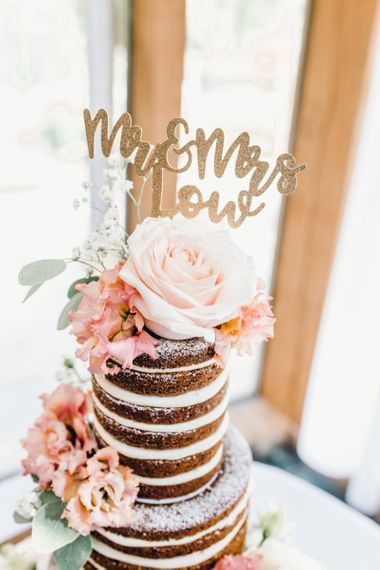 Naked three tier wedding cake with pink roses and a gold cake topper