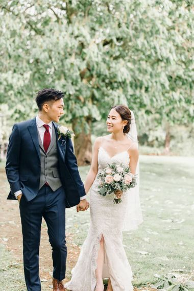 Bride and groom steal a moment at wedding reception with rose and gypsophila bouquets