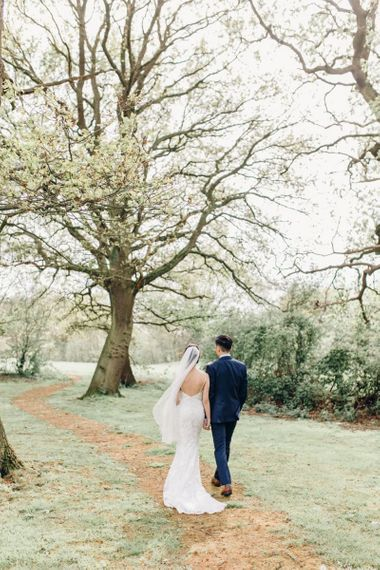 Back of brides lace dress with long veil