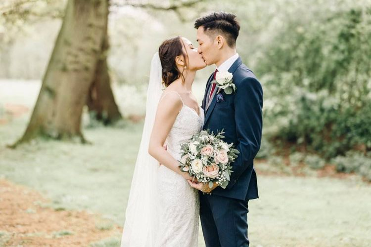 Bride wearing a delicate lace dress with rose and gypsophila bouquets  and groom in three piece suit with grey waistcoat
