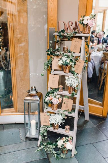 Rustic styled table plan with rose gold detailing and gypsophila arrangements