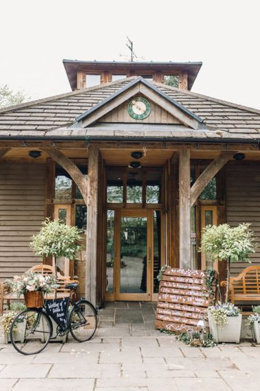 Entrance to wedding reception with rustic wedding bike and wooden pallet sign