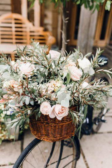 Beautiful pink rose flower arrangements in the basket of a rustic wedding bike sign
