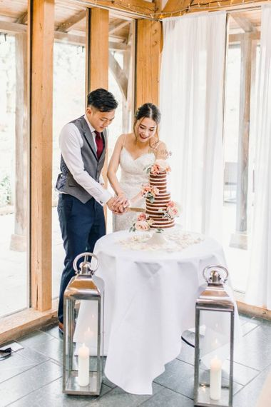 Bride and groom cut the naked wedding cake with dusky pink rose detailing and tall candle lanterns