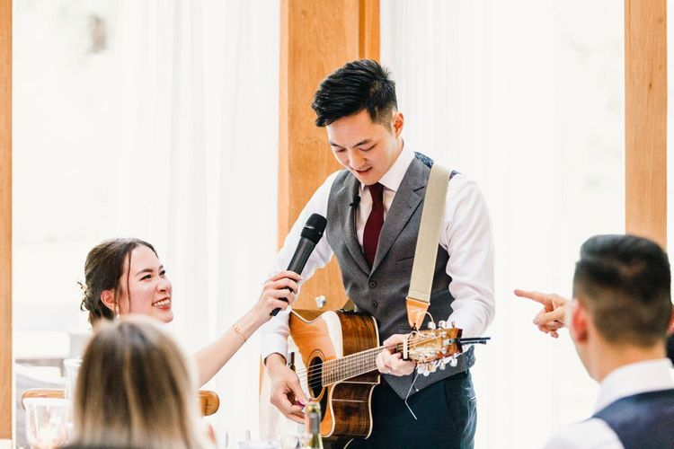 Groom serenades his bride with a guitar performance at wedding reception speeches