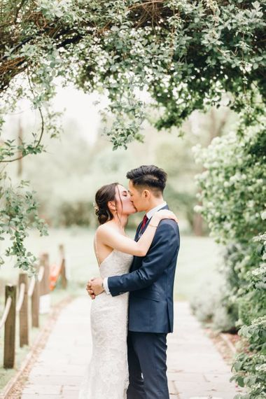 Bride and groom steal a moment with gypsophila archway