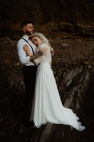 Groom with braces and tattoos embracing his boho bride