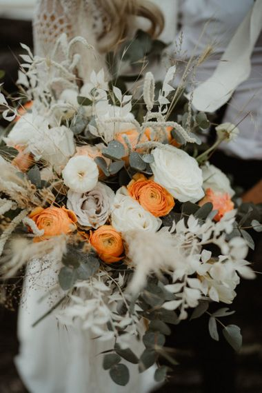 White and orange wedding bouquet with dried grasses and foliage