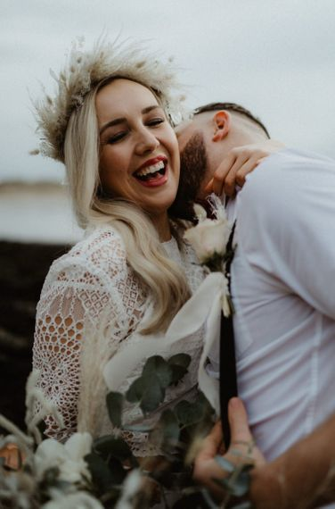 Boho bride with dried grasses flower crown laughing