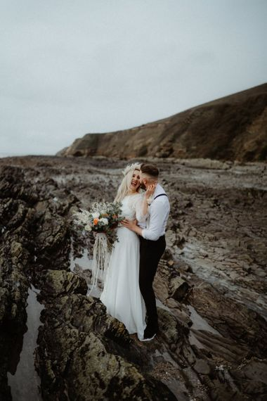 Boho bride and groom embracing on the cliffs at Devon elopement