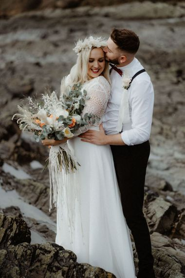 Portrait of groom kissing his brides forehead at Devon elopement