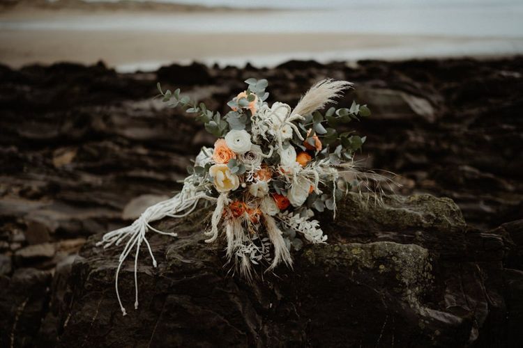 Boho wedding bouquet with white and orange flowers, foliage and dried grasses
