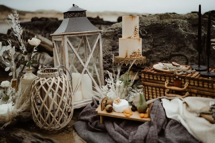 Devon elopement picnic with shell wedding cake and lanterns