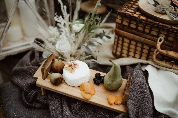 Wooden cheese board and dried fruits at Devon elopement