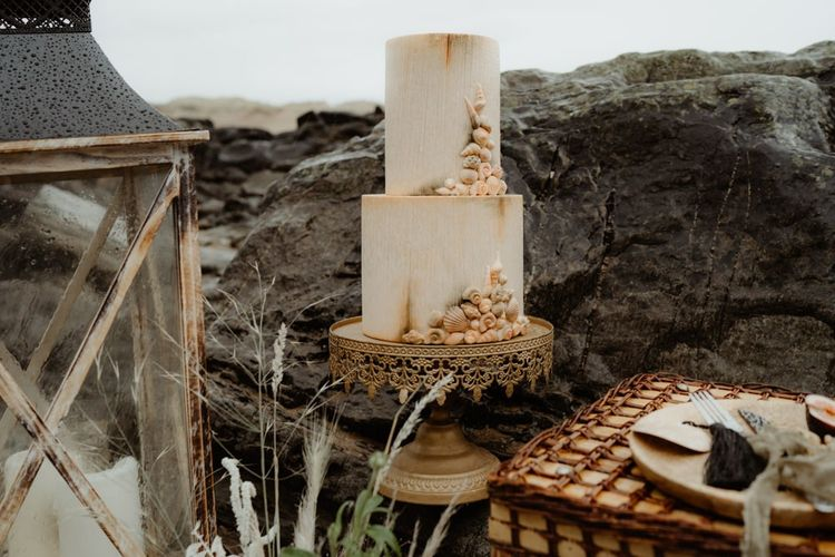 Ornate wedding cake with shell design for beach elopement