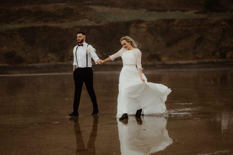 Boho bride and groom walking through the shore at their beach, Devon elopement