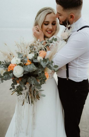 Boho wedding bouquet with eucalyptus, roses and macrame tie