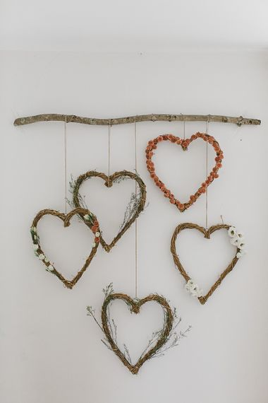 Floral heart wreaths on rustic branch for wedding photo booth backdrop