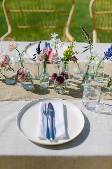 Wedding table place setting using single stems of vibrant spring flowers, oatmeal linen tablecloth and jute table runner