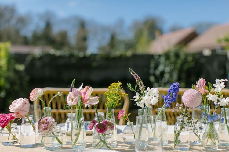 Wedding centrepiece for an outdoor garden wedding using single stems of spring flowers