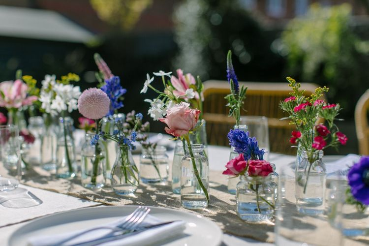 Wedding centrepiece created using single stems of roses, hyacinth and forget-me-nots in mini glass vases
