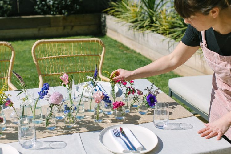 Person putting the finishing touches to a floral wedding centrepiece using vibrant colourful flowers for a garden wedding