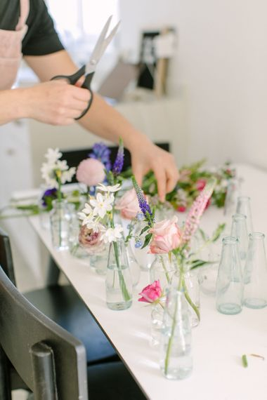 Person arranging single stems of flowers in glass vases and milk bottles to create a wedding centrepiece