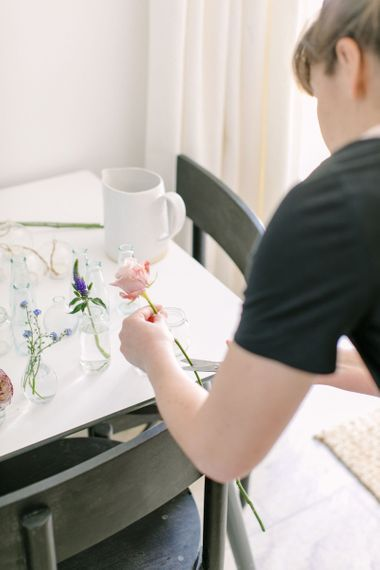 Person cutting an antique pale pink rose for a floral wedding centrepiece