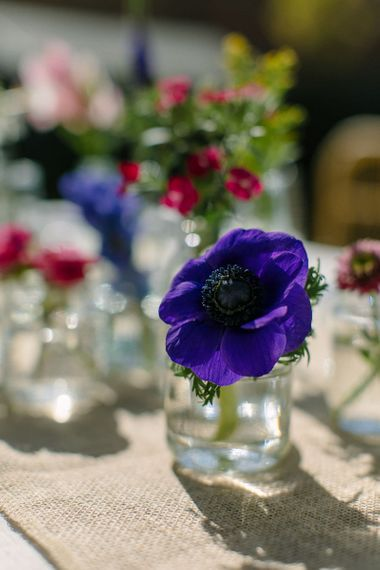 Close up of a vibrant purple anemone in a bud vase as part of a floral wedding centrepiece