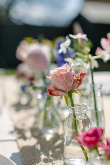 Close up of a single pale pink antique rose in a mini glass milk bottle vase as part of a wedding centrepiece