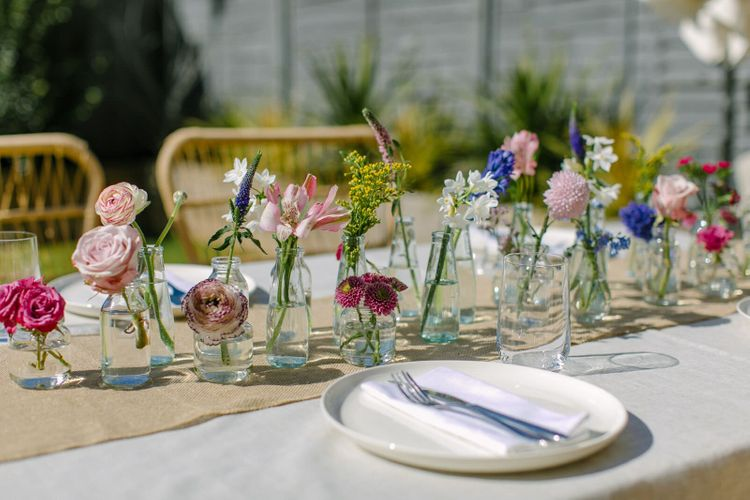 Table laid using neutral fabrics and tableware, and with a floral centrepiece made up of single stems in small glass vases