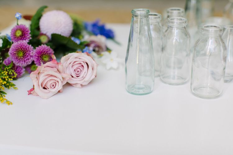 Freshly cut roses, wax flowers and mini chrysanthemums laid next to an assortment of clear glass vessels