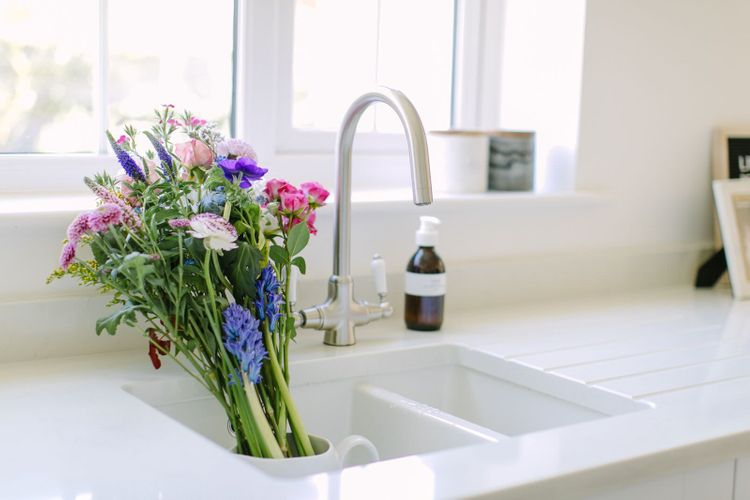 Bouquet of fresh spring flowers in vibrant shades of pinks, blues and purples, standing in an undermount ceramic sink