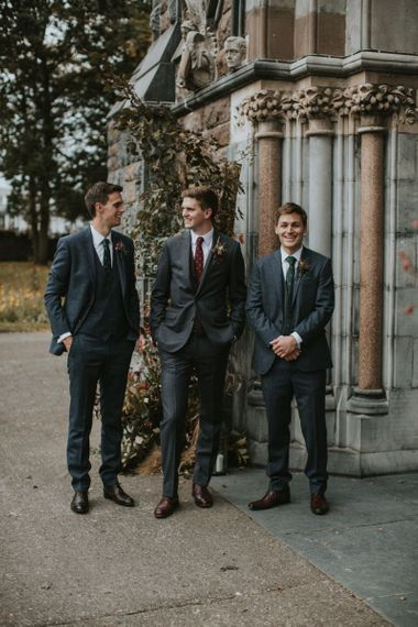 Groomsmen in Three-piece Navy Suits Standing Outside the Church
