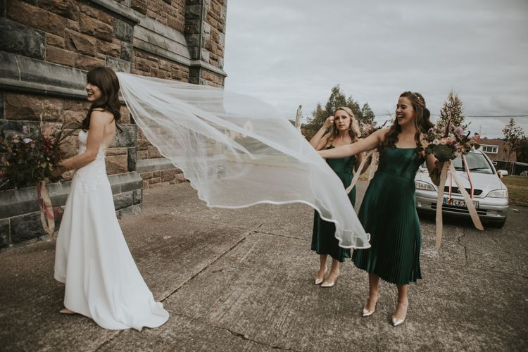 Bridal Party with Bride in High Low Elbeth Gillis Wedding Dress and Veil and Bridesmaids in Pleated Skirt Emerald Green Dresses
