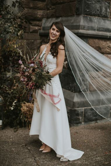 Beautiful Bride in High Low Elbeth Gillis Wedding Dress and Veil Holding an Oversized Autumn Bouquet