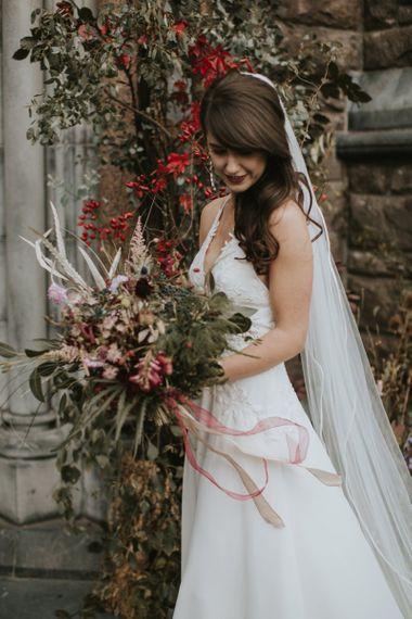 Bride in Elbeth Gillis Wedding Dress Holding a Deep Red and Green Wedding Bouquet