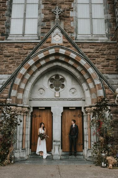 Bride and Groom Standing Outside the Church