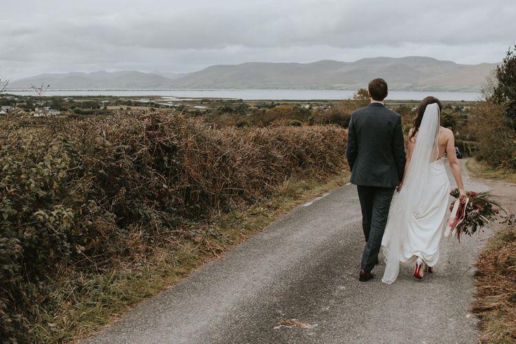 Bride in Elbeth Gillis Wedding Dress and Groom in  Tweed Suit Walking on a Country Road