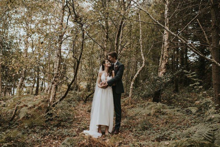 Groom in Tweed Suit  Embracing His Bride in Elbeth Gillis Wedding Dress in the Woods