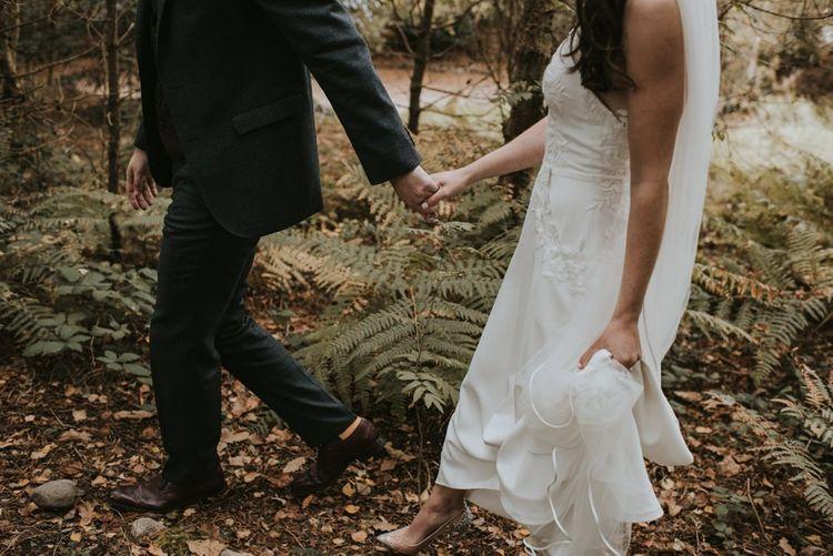 Bride in Elbeth Gillis Wedding Dress and Groom in  Tweed Suit  Hand in Hand Through The Woods