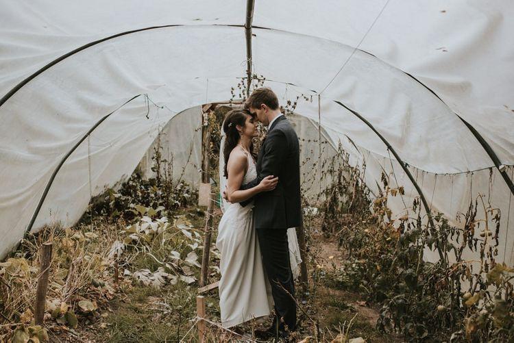 Bride in Elbeth Gillis Wedding Dress and Groom in  Tweed Suit  Embracing in a Greenhouse