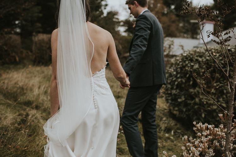 Bride in Elbeth Gillis Wedding Dress and Groom in  Tweed Suit  Holding Hands