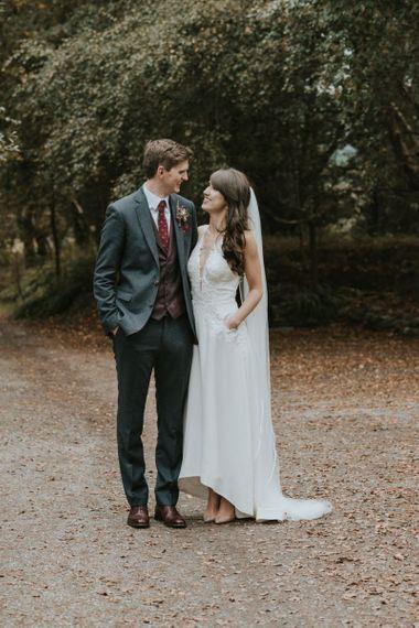 Bride in Elbeth Gillis Wedding Dress and Groom in  Tweed Suit  Arm in Arm