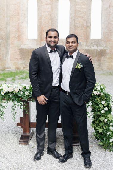 Groom and Groomsman in Black Tie Suits