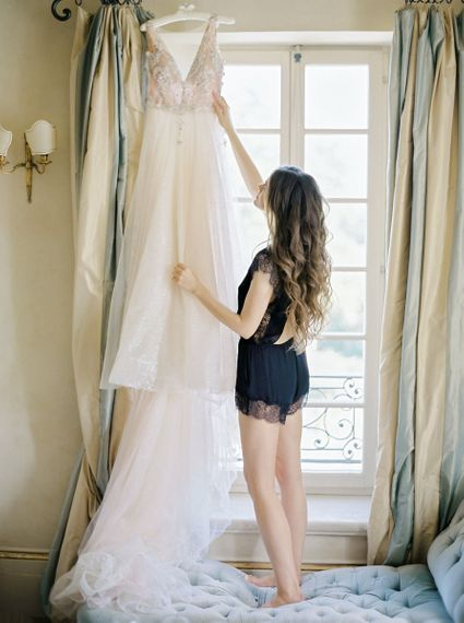 Wedding Morning Bridal Preparations with Bride in Black Lingerie Looking at Her Wedding Dress