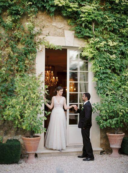 Groom in Black Tuxedo Escorting his Bride in a  Rara Avis Wedding Dress
