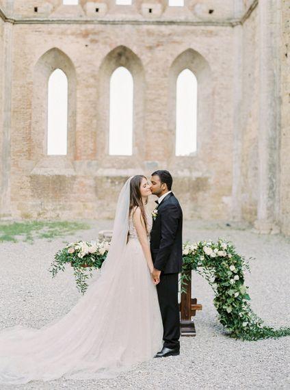 Groom in Black Tie Suit Kissing His Bride in a Rara Avis Wedding Dress