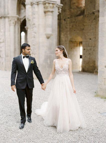 Bride in a Rara Avis Wedding Dress and Groom in Black Tie Suit Walking Through Their Open Air Church Wedding Ceremony Venue